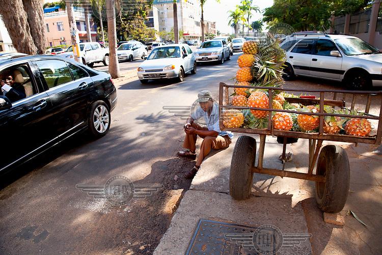 A man driving a Mercedes-Benz car passes a pinapple vendor sitting at the roadside.