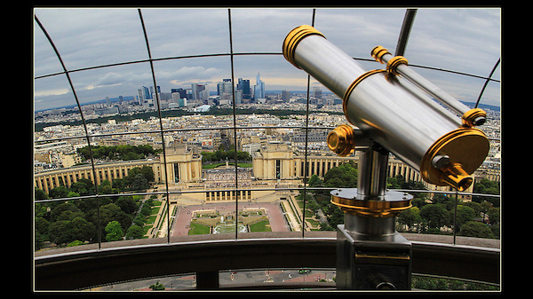 France, Paris.  <br /> Step back and make a composition that invites the viewer into the image, so they can imagine being there. Telescopes are personal icons, I make it a point to add them to my images because they often work. The wire fencing helps diminish a cloudy sky. Telescope and downtown Paris from Eiffel Tower.