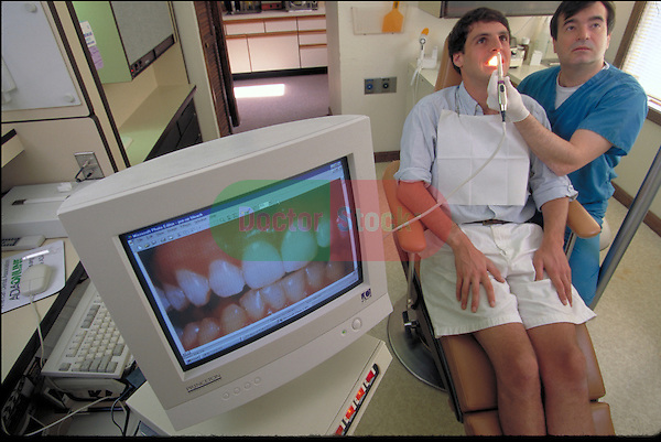 dentist with patient in chair viewing teeth on monitor