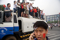 Spectators stand on a street cleaning truck as they watch the Nanjing, China, leg of the 2008 Olympic Torch Relay.