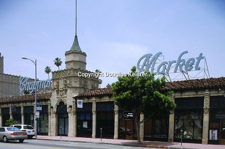 he Los Angeles architectural firm of Morgan, Walls, and Clements designed some of the most elaborate examples of Churrigueresque commercial architecture extant.  This building, built in 1929 as part of a complex known as Chapman Park Market, provides a case in point.  The upper reaches of the massive  tower are writhing with Churrigueresque ornament, while the areas of wall not otherwise embellished are covered in ashlar-patterned terra cotta blocks of varying relief.  Like many large firms, Morgan, Walls, and Clements employed numerous detail draftsmen whose job it was to copy ornament from photographs or pattern books and transfer it onto the building plans.  <br /><br />Still, architectural drawings necessarily could give only a rough indication of the architect's intent; it remained for artisans skilled in the various ornamental crafts to interpret and carry out the work.  Hence, sumptuous buildings such as this one stand as a monument to the workmanship of the era's craftsmen, without whom the demanding details of Revivalist architecture could never have been realized.  The exterior decorative arts involving masonry, stucco, cast-stone, terra-cotta, woodcarving, and wrought iron were at their zenith during the 1920s, as were interior finish crafts such as graining and marbling, gold leaf, and stencil-painting.  Many of these crafts lay dormant for a half-century before being rediscovered by appreciative artisans in the 1970s.