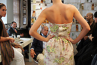 OSCAR de la RENTA, surrounded by members of his design team, reviews a piece for his Spring 2006 design collection on fit model in his studio.  Seated at left, is the company's CEO, Alex Bolen,  De la Renta's son-in-law.  550 Seventh Av., NYC.  Newsday/ARI MINTZ  8/31/2006.