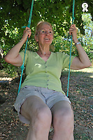 Senior woman swinging in garden, smiling (Licence this image exclusively with Getty: http://www.gettyimages.com/detail/91875445 )