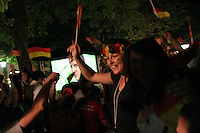 A German National Soccer Team fan cheers and waves a small German flag after Germany defeated Poland 1-0. She was among thousands that watch the match on a large outdoor screen at a beer garden in Munich, Germany on Wednesday, June 14th, 2006.  The win secured Germany a birth into the second round of the FIFA World Cup.
