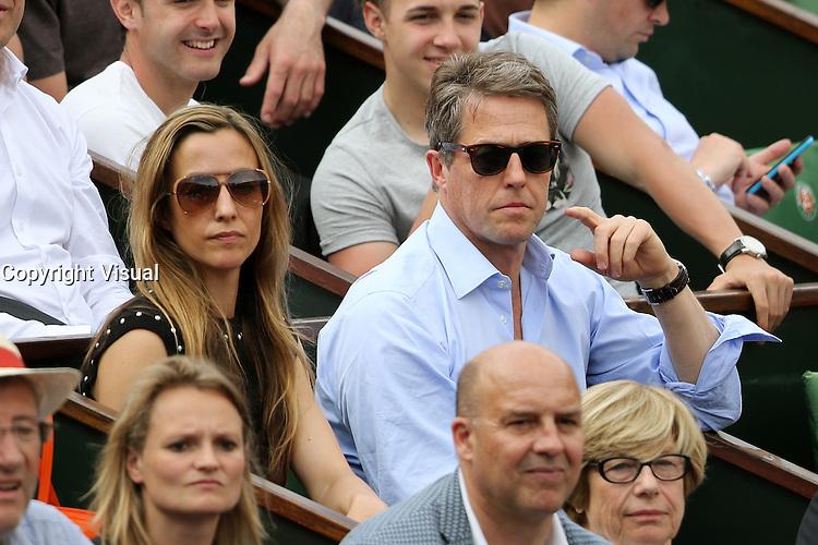Anna Eberstein and Hugh Grant watching tennis during Roland Garros tennis open 2016 on may 25 2016.