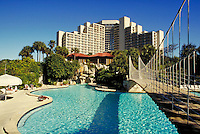 The Hyatt Regency Grand Cypress Resort Hotel, with its large, freeform swimming pool featuring a suspension bridge. Resorts, vacations, architecture. Florida.