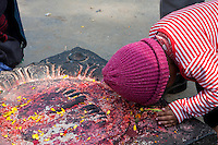 Nepal, Kathmandu, Swayambhunath.  Worshiper Bowing to the Feet of Buddha at the Foot of the Hill with the Stupa on top.  Offerings of Rice and Red Kumkuma Powder are on the Monument.