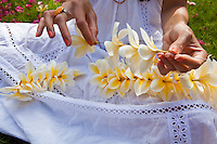A Hawaiian woman making a fragrant plumeria lei on the lawn