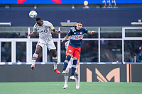 FOXBOROUGH, MA - JULY 25: Victor Wanyama #2 of CF Montreal and Gustavo Bou #7 of New England Revolution compete for a high ball during a game between CF Montreal and New England Revolution at Gillette Stadium on July 25, 2021 in Foxborough, Massachusetts.