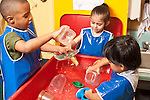 Education Preschool 3-4 year olds two boys and a girl wearing smocks playing separately at water table