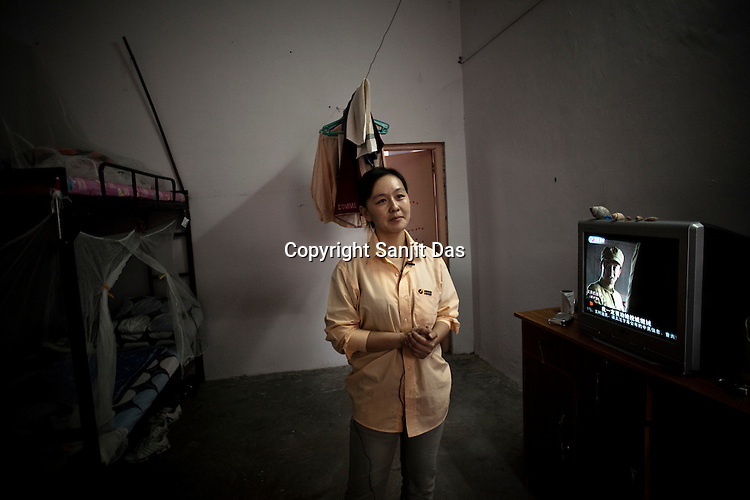25 year old Chinese interpreter, Li Wez Wez poses is seen in her dormitory  in the Chinese Colony of the Adani Power Plant in Mundra port industrial city of Gujarat, India. Indian power companies have handed out dozens of major contracts to Chinese firms since 2008. Adani Power Ltd have built elaborate Chinatowns to accommodate Chinese workers, complete with Chinese chefs, ping pong tables and Chinese television. Chinese companies now supply equipment for about 25% of the 80,000 megawatts in new capacity.