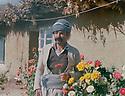 Iraq 1985 .A peshmerga holding a flower in front the political bureau of Kurdistan Socialist Democratic party in Kawlan, Qandil mountains .Irak 1985 .Un peshmerga avec une fleur pose devant le bureau politique du parti socialiste democratique du Kurdistan a Kawlan, montagnes de Qandil