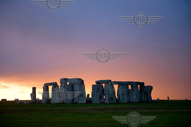 The setting sun sinks behind the standing stones during the winter solstice at Stonehenge near Amesbury.
