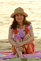 Jewish woman in mid thirty's sitting on towel at the beach wearing a hat and a flower leis