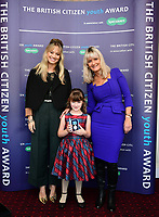 Pictured: Elly Neville with (C) presented The British Citizen Award for the Good of the Country by Kimberly Wyatt (L) and First News newspaper editor Nicky Cox.<br /> Re: Seven-year-old Elly Neville who was born despite doctors saying her parents would not be able to have any more children, has raised over £150,000 for the cancer ward that treated her father.<br /> Her parents Lyn and Ann had been told they were unlikely to have more children after he underwent a bone marrow transplant in 2005. <br /> Mr Neville subsequently spent a lot of time on the Ward 10 cancer facility at Withybush Hospital in Haverfordwest, Pembrokeshire.<br /> But four years later they were stunned when his painter and decorator wife Ann fell pregnant again.