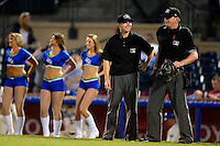 Umpires Ryan Wills and Lewis Williams (right) in between innings as dancers perform on the field during a game between the Lexington Legends and Greenville Drive on April 18, 2013 at Whitaker Bank Ballpark in Lexington, Kentucky.  Lexington defeated Greenville 12-3.  (Mike Janes/Four Seam Images)