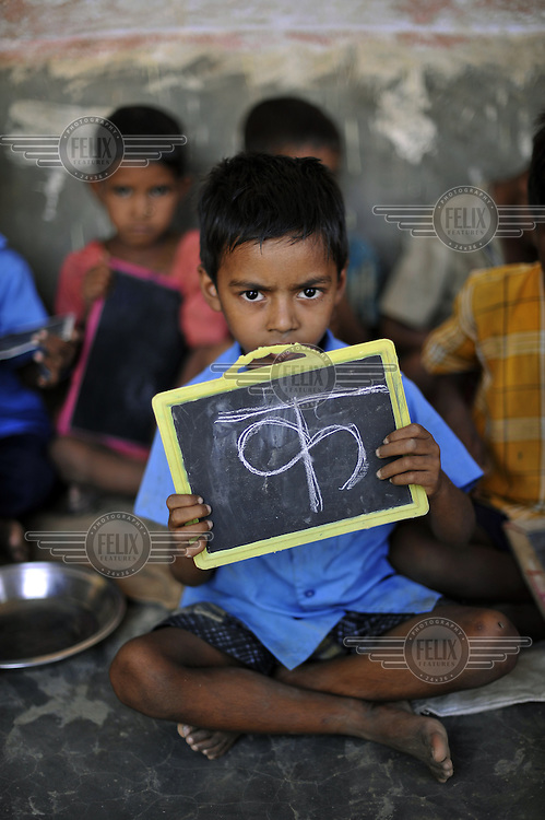 Children attend a class at the local school in Jalhe Bhongia Village. A young boy shows his chalkboard, which has the first character 'Kha' of the Hindi alphabet written on it.