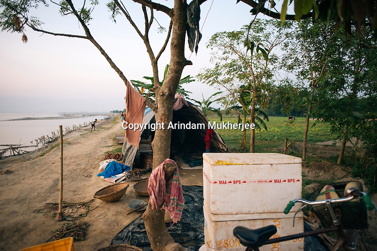 Belonging of a family are kept scattered on the pathway beside a make-shift tent made from the plastic sheet (tirpal) given by the government to erosion victims. Hossenpur village, Murshidabad District, West Bengal, India.
