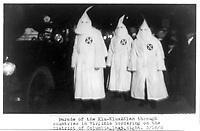 1922 March 18. - Three Ku Klux Klan members standing beside automobile driven by Klan members.- Parade of the Klu [sic] Klux Klan through counties in Virginia bordering on the District of Columbia last night