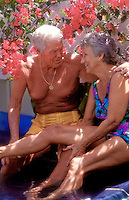 A fit, attractive senior couple in swim suits converse with brilliant red bougainvillea behind them.