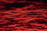 Sunset toward New Jersey from Mount Moses on Staten Island, NY. Blazing red mackeral sky with plane approaching Newark airport