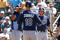 Tampa Bay Rays outfielder Ben Zobrist #18 is greeted at home plate by Jose Molina (left) and Will Rhymes (right) after hitting a grand slam home run during a spring training game against the Minnesota Twins at Hammond Stadium on March 26, 2012 in Fort Myers, Florida.  The Rays defeated the Twins 10-4.  (Mike Janes/Four Seam Images)