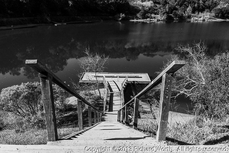The railing and steps leading to a fishing pier are cast in black and white revelaing details in grain and shadow.