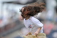 A young girl's hair flies around her head as she participates in a between-innings sack race during a game between the Charleston RiverDogs and the Greenville Drive on Sunday, August 16, 2015, at Fluor Field at the West End in Greenville, South Carolina. Charleston won, 6-2. (Tom Priddy/Four Seam Images)
