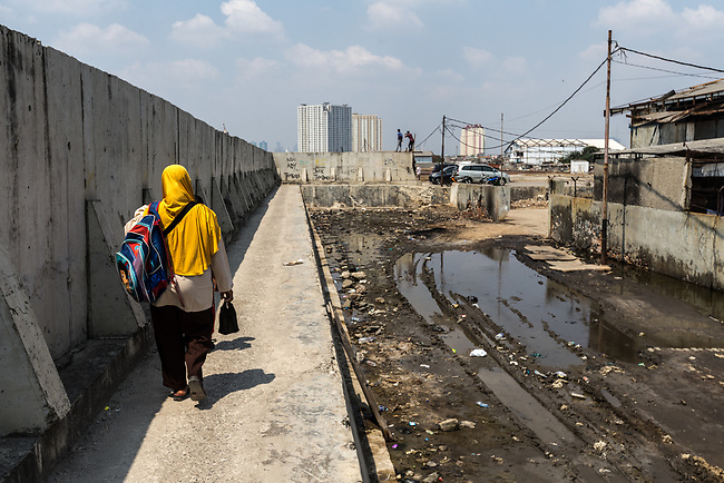 13 August 2019, Jakarta, Indonesia: A woman walks beside the protective seawall barrier keeping the ocean at bay at Muara Baru, North Jakarta. Local residents were speaking about the lack of water facilities that the local poor population has access to. Water is hauled in each day by motorcycle and trucks and by hand to allow residents of the kampungs to  buy it for washing and to do laundry. Separate water is needed for drinking. The Jakarta Governor is proposing a program to send in trucks of water for the locals to get for free. They are living in villages below the seawater line on the coast of Jakarta that is sinking faster than anywhere else in the world so they have the position of being surrounded by water yet not having access to clean supplies. Picture by Graham Crouch/The Australian