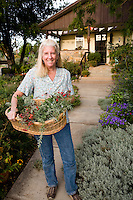 Tammi Hartung with fresh basket of herbs at her Colorado home