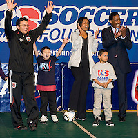 First Lady Michelle Obama and US Soccer Foundation President and CEO Ed Foster-Simeon celebrate a goal during a US Soccer Foundation clinic held at City Center in Washington, DC.