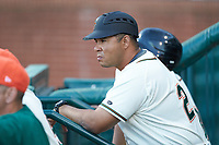 Greensboro Grasshoppers manager Miguel Perez (29) watches from the dugout during the game against the Hagerstown Suns at First National Bank Field on April 6, 2019 in Greensboro, North Carolina. The Suns defeated the Grasshoppers 6-5. (Brian Westerholt/Four Seam Images)