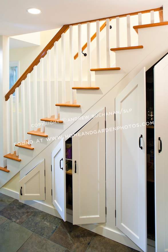 Custom cabinets built under the stairs maximize storage in this newly remodeled basement.