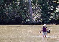 A visitor to Corcovado National Park wades across the Rio Claro.