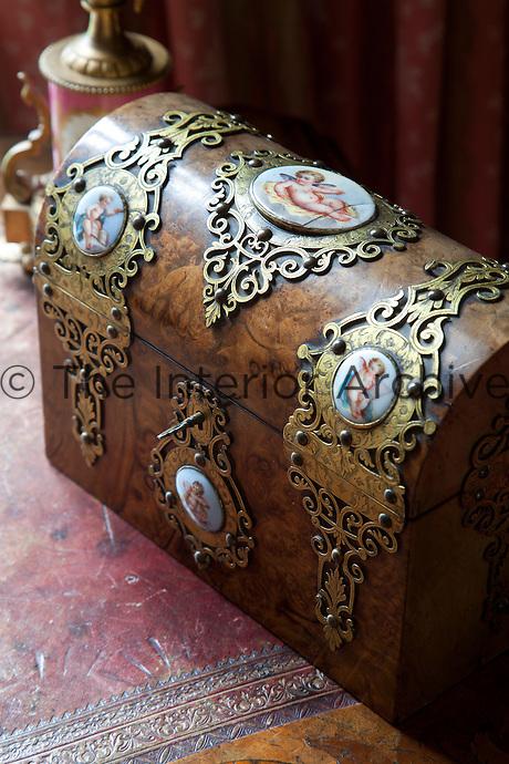 An antique walnut chest with enamel medallions featuring cherubs