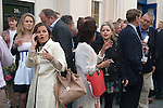 Belgravia London UK. Motcomb Street, annual street party, drinkers party goers outside the Pantechnicon building. Woman on mobile phone.
