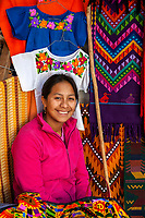 Chichicastenango, Guatemala.  Quiche Woman Selling Colorful Clothing and Wall Hangings.
