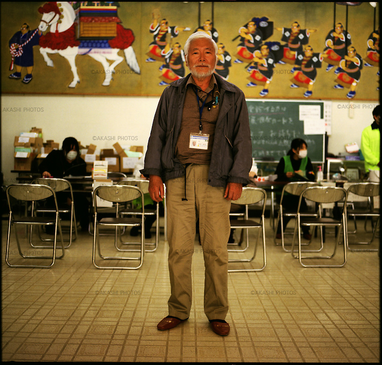 """Mr. Masaki Shimanuki, 68, a doctor of Rikuzentakata Hospital, in a makeshift hospital in a community center in one month after the tsunami and earthquake. He was in the hospital when the hospital was hit by the earthquake and tsunami. After the huge shake of the earthquake, he was trying to evacuate a person to the send floor as the hospital's disaster instruction says. When they reached to the second floor, """"Tsunami! Go up to the third floor!"""" someone shouted. When they reached the third floor, he saw tsunami from the window. """"It was not a wave. It was a wall of dark water,"""" he said. It was clear that the third floor was not high enough. He ran up to the forth floor. Then, the wall of water hit the hospital with a great shock. The water started to fill up the forth floor where he was and all hospitalized patients were on the bed. The doctors and patients who can move went up to the rooftop. When the water started to go down, he and other doctors went down to the forth floor to save the left bedridden patients. Only bedridden patients who were sleeping on the air mat that prevents them from bedsores were alive floating on the air mat in the water. They brought up only alive patients up to the rooftop. From the rooftop, he saw the town completely under the black water. There were about 100 people on the rooftop. Doctors and nurses tried artificial respiration on the dying patients. It started snowing. It was freezing. They put the disposal diaper around their bodies, and wore plastic bag over the diapers. Next day, all survivors were rescued by the helicopters. Three days after, doctors opened the makeshift hospital in a community center. Dr. Shimanuki, lost everything and lives in a shelter but started working in the makeshift hospital for his patients. """"I lost my white doctor coat as well, but I like this jacket what I wear now,"""" he said. """"It was in the box of relief supplies to the victims in the shelter. I really appreciate that."""""""