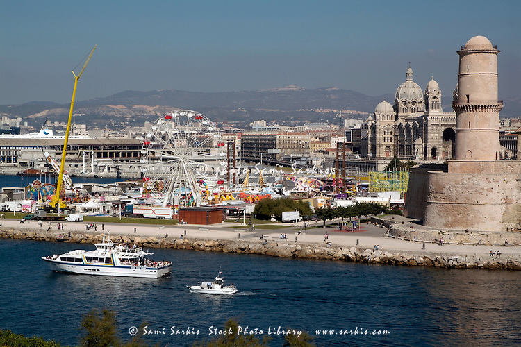 Amusement park on the waterfront next to the Fort Saint-Jean and the Marseille Cathedral, Marseille, France.