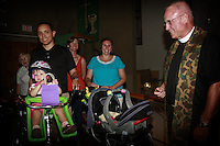 Saturday, September 20, 2008.  Pacific Beach, San Diego, CA, USA.  The Reverend Robert Crafts, MD prepares to perform a blessing on the wheels assmbled inside St Andrews Church during the annual Bessing of the Wheels ceremony.  Raul Cadena brought his daughter Isable and son Julian along on their bicycle for the blessing.