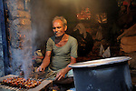 A Kebab seller at Katputly colony in New Delhi, India. 17.11.2009. Kathputly colony is a slum area in West Delhi. This slum seems like any other slum areas of modern India with dysfunctional electricity, non existing sanitation and poverty. As a part of Delhi, this is also ailed with water crisis. Large families live their lives crammed together in a single room with all the odds which complement poverty. One thing which differentiates this slum with any other is the people living in the colony. Nearly everybody in this slum is a traditional performing artist; and they have been migrating to this area for last 50 years from different parts of the country for a better livelihood. They are magicians, acrobats, jugglers, puppeteers, dancers and musicians. These artistes perform in star rated hotels, marriage ceremonies of the richer section, functions, and festivities all around the country and the world. Most of the artisans I met here, have performed in Europe and America but such opportunities are rare to come by. They struggle to keep their art form alive. They say that they don't get any help or support from the government for their basic needs and for the well being of the Kathputly colony -  though they have uphold the prestige of the country internationally. Polluted air, dirty alleys smelling of urine, colourful dress and sound of music characterise Kathputly colony, which is the one of its kind in India. Arindam Mukherjee