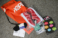 """The contents of a """"Hope Tote"""" are shown, Saturday, April 3, 2021 at Sam's Furniture in Springdale. Samaritan's Feet distributed approximately 720 pairs of shoes to pre-registered students from 18 elementary schools across Springdale in a """"drive-thru"""" event. Each recipient received a """"Hope Tote"""" drawstring book bag that contains a new pair of athletic shoes, socks, hygiene kit and a """"hope note"""" with an encouraging message submitted online from Samaritan's Feet supporters. Check out nwaonline.com/210404Daily/ for today's photo gallery. <br /> (NWA Democrat-Gazette/Charlie Kaijo)"""
