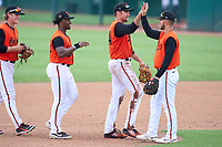 FCL Orioles Orange outfielders John Rhodes (49), Donta' Williams (48), and Colton Cowser (44) high five Connor Norby (1) after a game against the FCL Pirates Gold on August 9, 2021 at Ed Smith Stadium in Sarasota, Florida.  (Mike Janes/Four Seam Images)