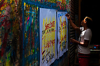 "A Colombian sign painter writes with a brush while working on music party posters in the sign painting workshop in Cartagena, Colombia, 16 April 2018. Hidden in the dark, narrow alleys of Bazurto market, a group of dozen young men gathered around José Corredor (""Runner""), the master painter, produce every day hundreds of hand-painted posters. Although the vast majority of the production is designed for a cheap visual promotion of popular Champeta music parties, held every weekend around the city, Runner and his apprentices also create other graphic design artworks, based on brush lettering technique. Using simple brushes and bright paints, the artisanal workshop keeps the traditional sign painting art alive."