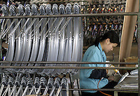 A worker makes bicycle fenders at the Shanghai Forever Bicycle Factory (SFBF) in Shanghai, China. Despite the government's efforts to encourage automobile ownership in recent years, the bicycle remains the most popular mode of transportation for China's masses. The SFBF, it's products once a must have and a symbol of status for every Chinese family, are now supplying bicycles to countries around the world. It has seen it's sales increase 59% percent in the past year to 876 million yuan (euro 89.36 million)..21-APR-04