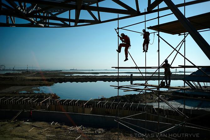 Workers climb on scaffolding on a building under construction on Kazar Islands in the region Qaradagh, Azerbaijan. Kazar is a massive artificial island project, following the spirit of man-made islands in Qatar.