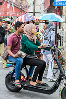 George Town, Penang, Malaysia. Young Malaysian Couple Riding a Motorscooter.