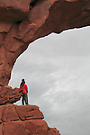 Couple standing at North Window  Arch in Windows Area, Arches National Park, Moab, Utah, USA. .  John offers private photo tours in Arches National Park and throughout Utah and Colorado. Year-round.