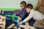 Education Preschool 4 year olds two boys playing together with blocks and vehicles