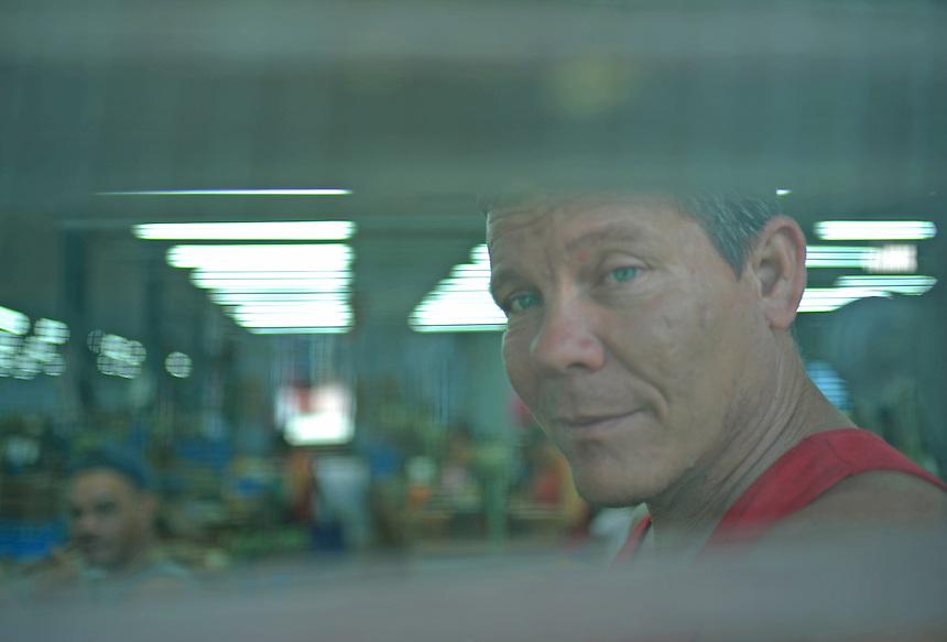 A roller seen through a screened window at the Constantino Perez Carrodegua cigar factory in Santa Clara, Cuba. MARK TAYLOR GALLERY